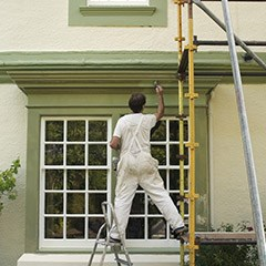 Man on scaffold painting exterior