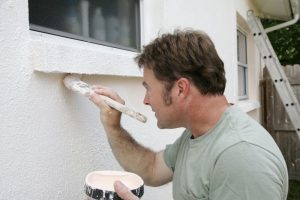 A man painting his home's exterior.