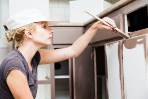A woman painting her kitchen cabinets.