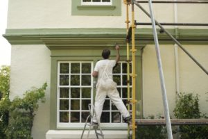 professional painter painting the outside of a house